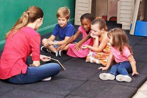 Gruppe Kinder redet über ein Buch im Kindergarten mit der Erzieherin